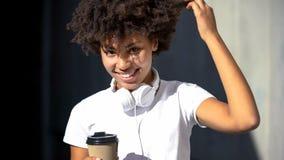 Беспечальная афро-американская женская держа чашка чаю и усмехаться в камеру, flirt стоковое изображение rf
