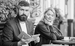 Flirt и дата Встреча людей с подобными интересами Человек и женщина сидят терраса Находка общего интереса литературы стоковые изображения