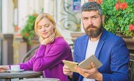 Flirt и дата Встреча людей с подобными интересами Человек и женщина сидят терраса Находка общего интереса литературы стоковое фото