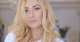 Flirt-blonde Frau, welche die Kamera betrachtet Stockbilder