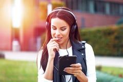 Flirt en ligne de femme et musique de écoute extérieurs Images stock