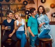 Flirt et boisson de jumeaux avec leurs amies à la barre Images libres de droits