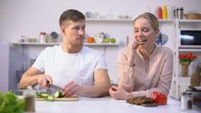 Flirt felice delle coppie, cucinante insalata degli ortaggi freschi, alimento libero sano del gmo video d archivio