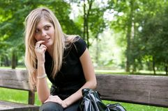 Flirt - Young woman siting on bench Royalty Free Stock Photos