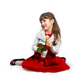 Flirtatious girl with orchid. Flirtatious cute girl with orchid in hands dressed in red sits on folded cover. Portrait on white bacground with light shadows royalty free stock photography