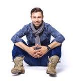 Flirtatious man sitting on floor. Flirtatious man sitting on the floor stock photography