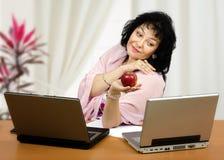 Flirtatious woman holding red apple. Flirtatious mature woman is holding red apple in front of two laptops royalty free stock image