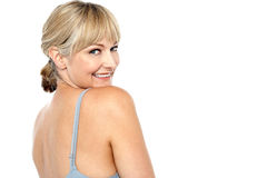 Flirtatious woman turning back and passing a smile. To you. Isolated against white background stock images