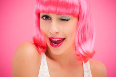Flirtatious woman winking. Woman wearing wig over pink background Royalty Free Stock Images