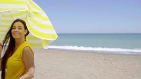 Flirtatious young woman holding a beach umbrella stock video