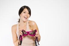 Flirtatious young woman holding a sexy bra Stock Photos