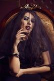 Flirtend Frau im schwarzen transparenten Schleier, der im Weinlesestuhl sitzt stockfotografie
