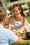 Flirtenholdinghände der Paare am Kaffeestab Stockbilder