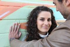 Flirterig paar dat door muur wordt bevonden Stock Foto's