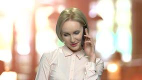 Flirterige blondevrouw die op celtelefoon spreken stock video