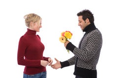 Flirting. Beautiful young couple flirting with colorful flowers on white stock image