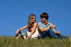 Flirting. Two teens sit on a hill surrounded by vivid blue sky.  Both are back to back but looking over their shoulders at each other Royalty Free Stock Photo