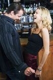 Flirting. Attractive blond woman laughs at her handsome partner's jokes at a bar Royalty Free Stock Images