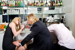 Flirting at a bar. Three young adults sitting at a bar; one sleeping, the others flirting with each other Stock Image