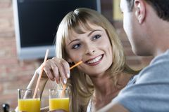 Flirting in the bar. Smiling cute blond woman listening to her male companion while drinking orange juice in the bar Stock Images