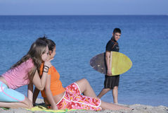 Flirting on beach. Two teens watch as surfer walks past on beach Royalty Free Stock Photo