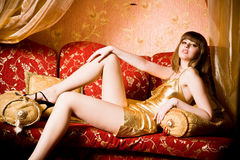 Flirting beautiful woman in golden dress Royalty Free Stock Photography