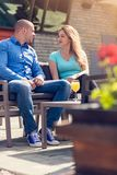 Flirting in a cafe. Beautiful loving couple sitting in a cafe enjoying in coffee and conversation. Love, romance, dating royalty free stock image