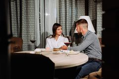 Flirting in a cafe. Beautiful loving couple sitting in a cafe enjoying in wine and conversation. Love and romance. royalty free stock photos
