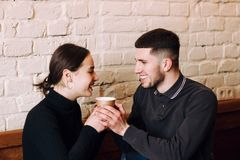 Flirting in a cafe. Beautiful loving couple sitting in cafe enjoying in coffe and conversation royalty free stock photos
