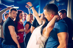Flirting in the club. Group of young people on a party, couple is flirting while dancing royalty free stock photo