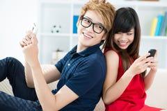 Flirting/communicating. Flirty couple sitting back to back and communicating royalty free stock photos