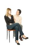 Flirting couple. Young girl sitting on a chair and a man smiling to her Stock Photography