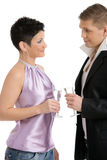Flirting couple. Trendy young couple clinking with champagne, looking each other, flirting. Isolated on white background Stock Photo