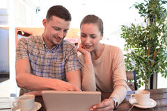 Flirting couple in cafe using digital tablet. Royalty Free Stock Images