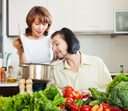 Flirting couple cooking together Royalty Free Stock Images