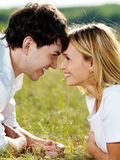 Flirting couple lying  in green meadow. Portrait of young happy  flirting couple lying  in green meadow and looking against each other Royalty Free Stock Photos