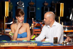 Flirting couple playing cards in a casino Stock Photos