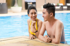 Flirting couple. Young Asian couple flirting in swimming pool Royalty Free Stock Photos