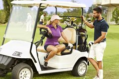Flirting on the fairway. Golfers flirting in the fairway in golf cart, smiling stock photos