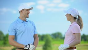 Flirting female and male golf players giving high-five after game, sympathy. Stock footage stock footage