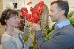 Flirting in flower shop. Flirting in the flower shop stock photo