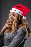 Flirting girl thinking about a gift for Christmas. On a Santa Claus hat Stock Image