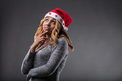Flirting girl thinking about a gift for Christmas. On a Santa Claus hat Royalty Free Stock Image