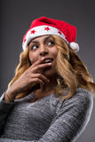 Flirting girl thinking about a gift for Christmas. On a Santa Claus hat Stock Images