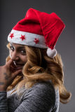 Flirting girl thinking about a gift for Christmas. On a Santa Claus hat Stock Photo