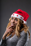 Flirting girl thinking about a gift for Christmas. On a Santa Claus hat Royalty Free Stock Images