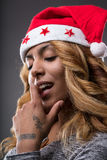Flirting girl thinking about a gift for Christmas. On a Santa Claus hat Royalty Free Stock Photos