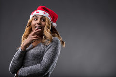 Flirting girl thinking about a gift for Christmas. On a Santa Claus hat Royalty Free Stock Photo