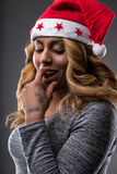Flirting girl thinking about a gift for Christmas. On a Santa Claus hat Royalty Free Stock Photography