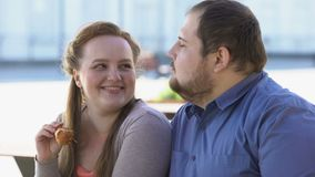 Flirting girlfriend feeding fat boyfriend with fried chicken, obesity problem. Stock footage stock footage